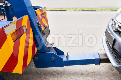 Tow truck towing a broken down car on the street Stock Photo