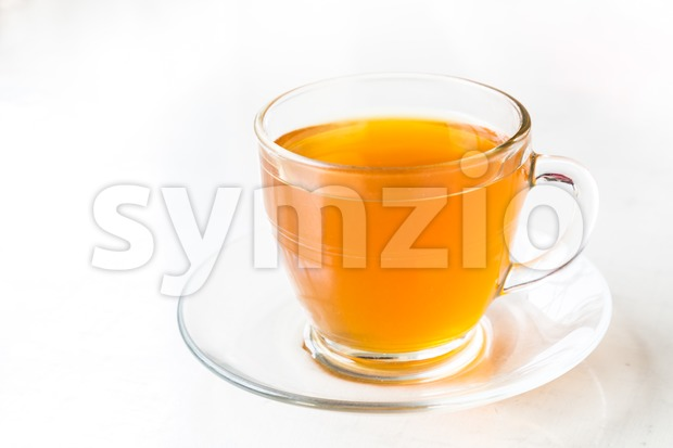 Hot aromatic honey tea in transparent cup and saucer Stock Photo
