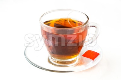 Hot tea with tea bag in transparent cup and saucer Stock Photo