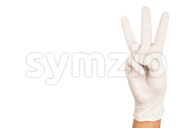 Hand in surgical latex glove gesture number Three. Stock Photo