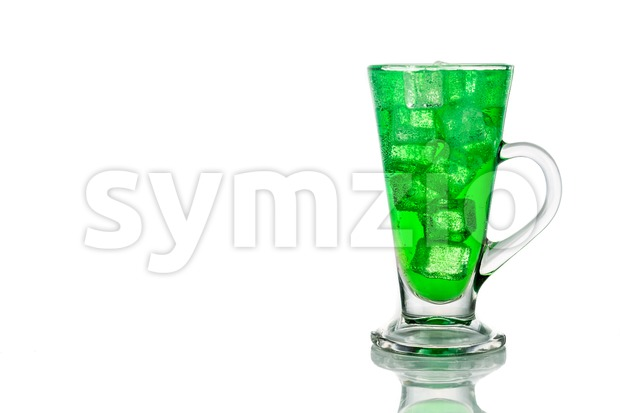 Refreshing green fizzy soft drink with ice in transparent glass.