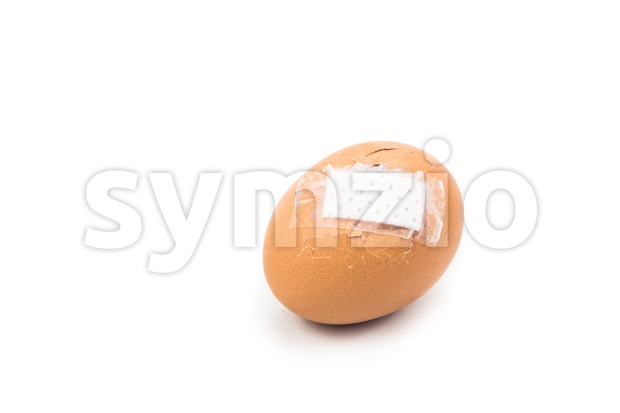 Concept of cracked egg shell with bandage on cracked area. Stock Photo