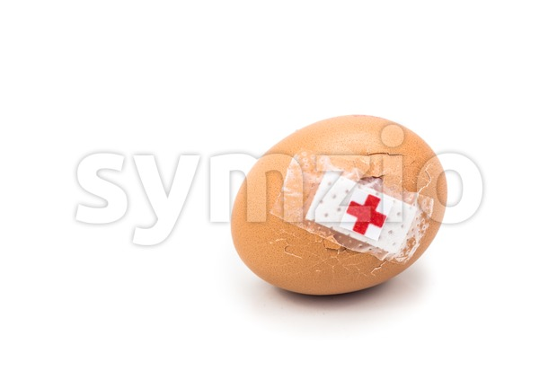 Concept of cracked egg with bandage with other eggs on tray