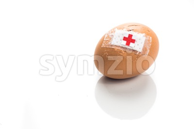 Concept of cracked egg with bandage with other eggs on tray. Stock Photo