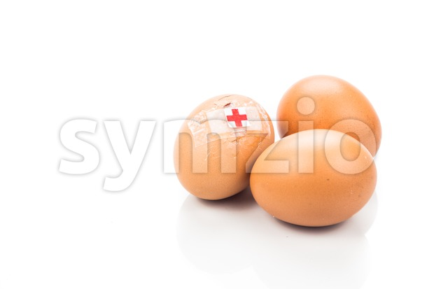 Concept of cracked egg with bandage next to two other eggs. Stock Photo
