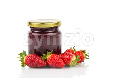 Organic strawberry jam in transparent glass jar with fresh strawberries Stock Photo