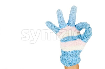 Hand in blue pink winter glove gesture OKAY against white background. Stock Photo