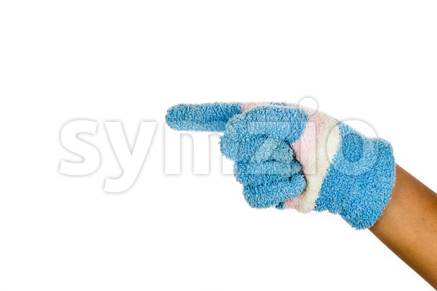 Hand in blue winter glove pointing direction against white background. Stock Photo