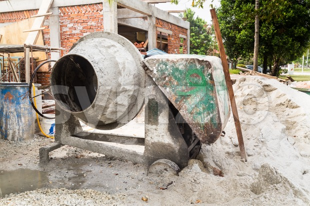 Cement concrete mixer with construction site in background Stock Photo