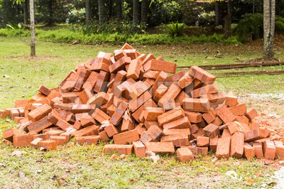 Heaps of red clay bricks at construction site Stock Photo