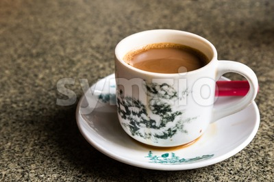 Traditional oriental Chinese coffee in vintage mug and saucer in soft focus setting with ambient light Stock Photo