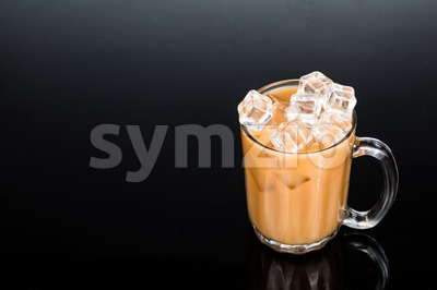 Refreshing ice cold tea with milk in transparent glass against dark background Stock Photo