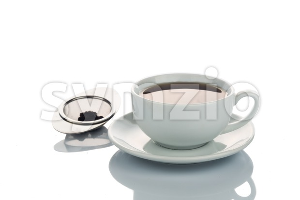 Freshly brewed hot tea in cup saucer with tea sieve Stock Photo