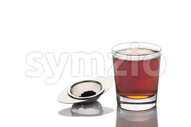 Freshly brewed hot tea in transparent glass with tea sieve Stock Photo