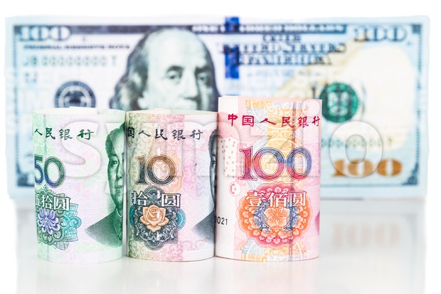 Close up of China Yuan Renminbi currency note against US Dollar.