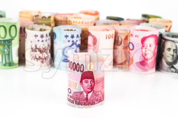 Pile of rolled-up currency notes with Indonesia Rupiah in front Stock Photo