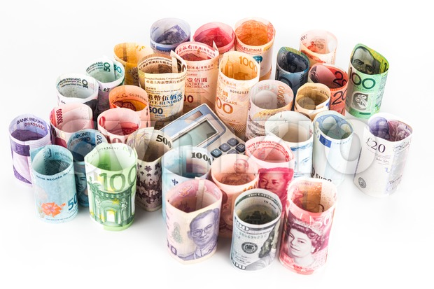 Pile of rolled-up currency notes with a calculator Stock Photo