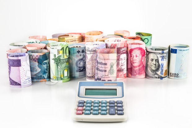 Pile of rolled-up currency notes with a calculator in foreground Stock Photo