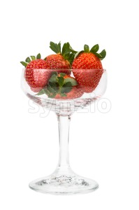 Juicy strawberries in a transparent cocktail glass with white background Stock Photo