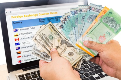 Hand sorting USD and Ringgit in front of currency exchange chart on computer screen Stock Photo