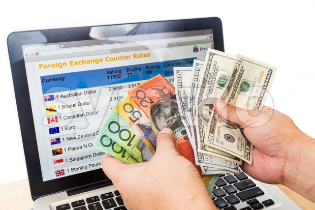 Hand sorting Australian dollar and USD in front of currency exchange chart on computer screen Stock Photo