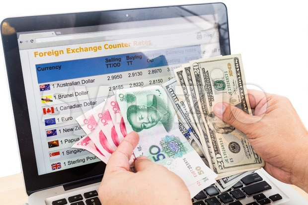 Hand sorting USD and Yuan in front of currency exchange chart on computer screen Stock Photo