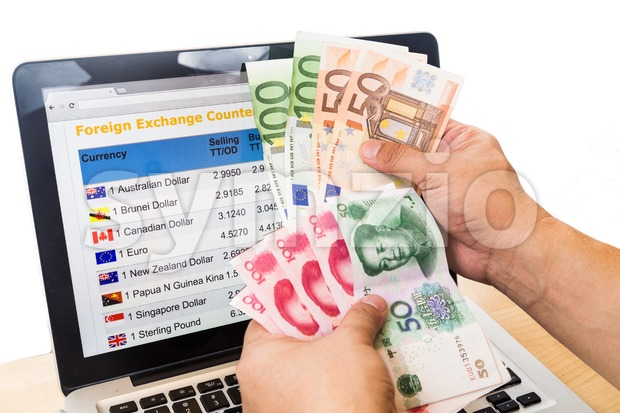 Hand sorting EURO and YUAN in front of currency exchange chart on computer screen Stock Photo