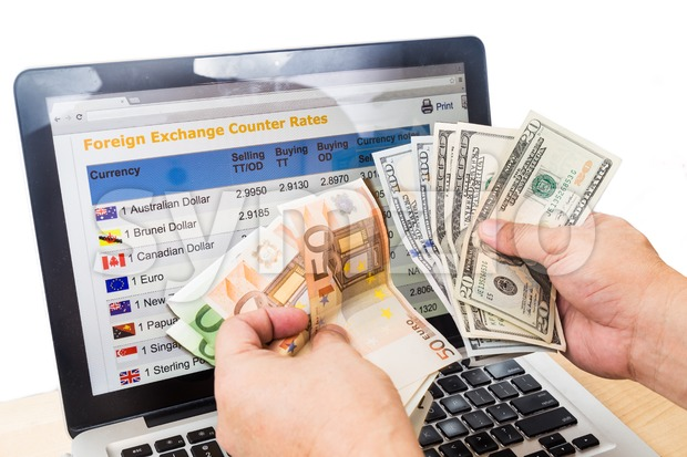 Hand sorting USD and EURO in front of currency exchange chart on computer screen Stock Photo