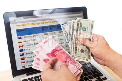 Hand sorting Indonesia Rupiah and US Dollar in front of currency exchange chart on computer screen Stock Photo