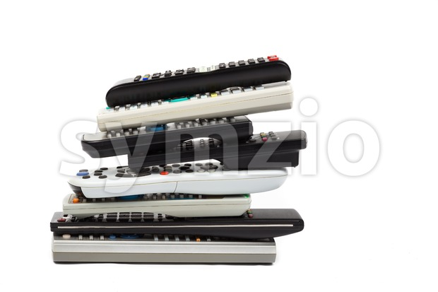 Stack of audio video remote control device in white background Stock Photo