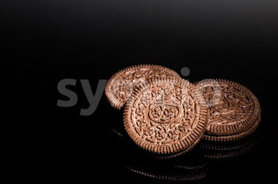 Creme-filled sandwich cookie on dark reflective background Stock Photo