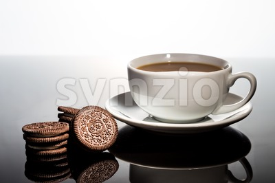 Creme-filled sandwich cookies and coffee cup on dark reflective background Stock Photo