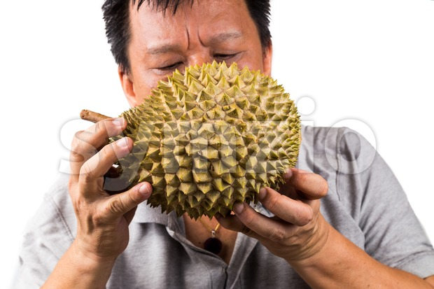 Man sniffing a durian fruit to assess its quality and ripeness