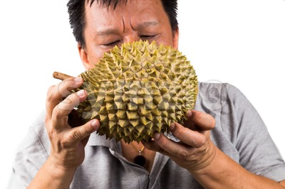 Man sniffing a durian fruit to assess its quality and ripeness Stock Photo