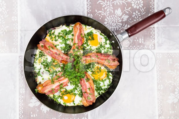 Delicious bacon strips, sausages and fried eggs breakfast meal with coriander served in a pan.