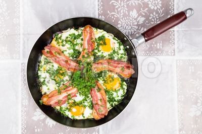 Delicious bacon strips, sausages and fried eggs breakfast in pan. Stock Photo