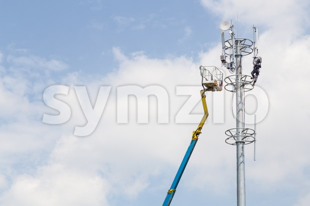 Worker installing mobile network antenna onto tall telecommunication tower with crane