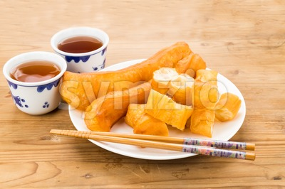Fried bread stick or You Tiao served with Chinese tea. Stock Photo